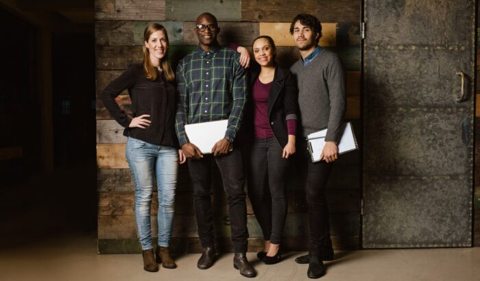Portrait of successful business team standing together against wooden wall. Full length image of a group of diverse colleagues standing in an office
