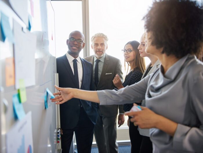 Group of mixed business people having a meeting using a white board in bright office space