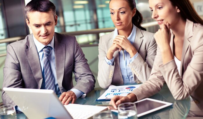 Group of confident business partners looking at laptop display at meeting